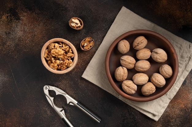 Целые грецкие орехи, треснутый грецкий орех и очищенные ядра с щелкунчиком на коричневой бетонной стене. здоровая еда