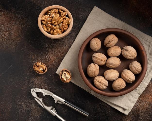 Неочищенные грецкие орехи, щелкунчик и очищенные ядра на коричневой стене. здоровое питание