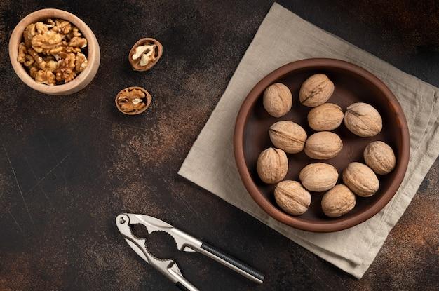Целые грецкие орехи в миску, щелкунчик и ядра на коричневой бетонной стене. органическая еда