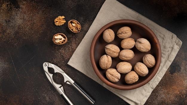Целые грецкие орехи и потрескавшийся орех с щелкунчиком на коричневой стене