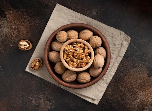 Неочищенные грецкие орехи и очищенные ядра в миску на коричневой стене. здоровая закуска
