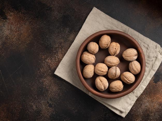 Грецкие орехи в скорлупе в глиняной табличке на текстурной стене.