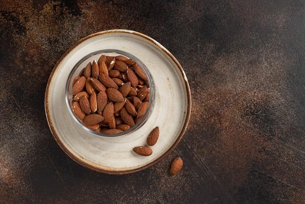 Миндальные орехи в стеклянной банке на темной текстурированной стене. ингредиент для приготовления пищи