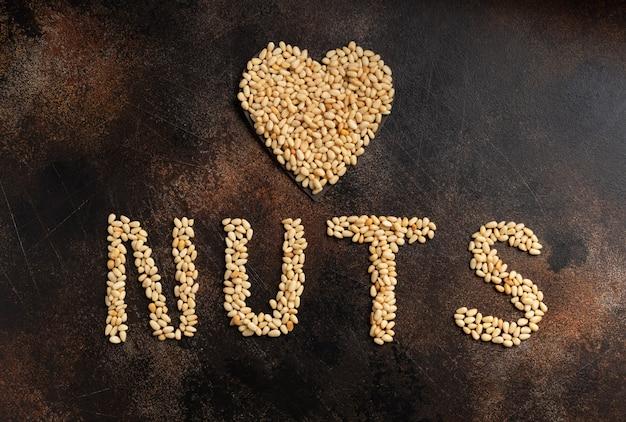 Надпись орехи и сердечко из очищенных кедровых орехов на коричневой бетонной стене
