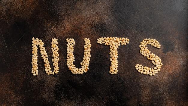Надпись орехи от ядра кедровых орехов на коричневой бетонной стене. пищевая стенка