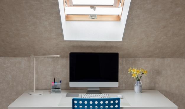 Белый стол с монитором, настольная лампа и ваза со свежими нарциссами. домашний офис