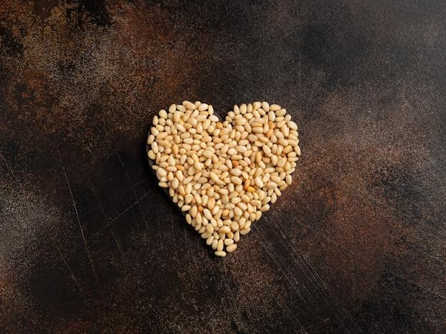 Ядра кедровых орехов в форме сердца на коричневой стене. здоровый образ жизни