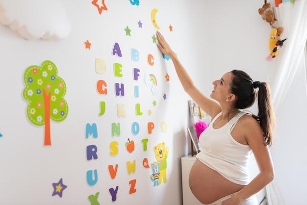 妊娠中の女性が赤ちゃん部屋の壁をレタリング