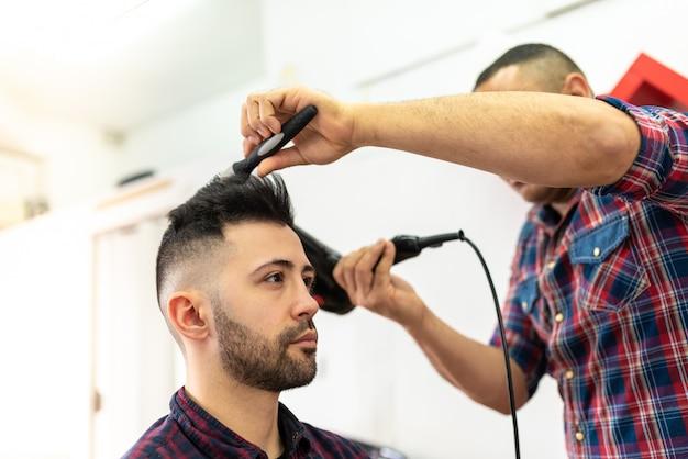 若い男が理髪店で髪型を取得