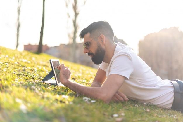 流行に敏感な男が公園でデジタルタブレットを使用して