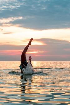 ビーチで水に飛び込む。