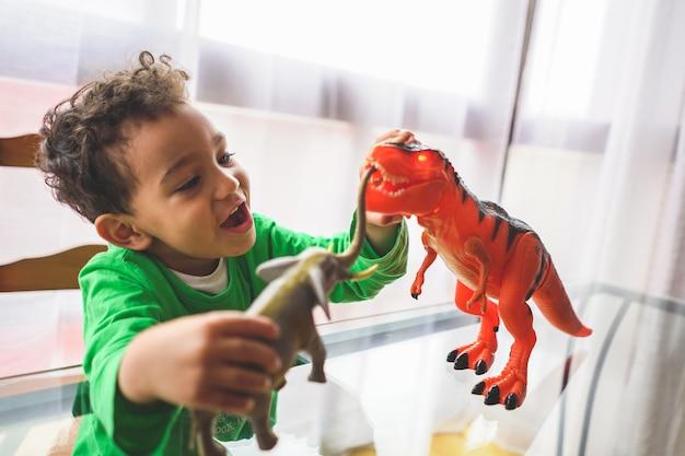 Латиноамериканский мальчик играет с игрушками животных у себя дома.