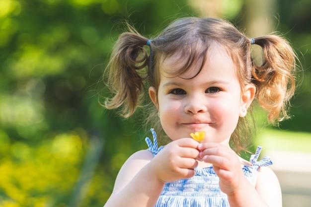 Маленькая девочка держит цветок на открытом воздухе.