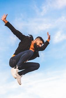流行に敏感な若い男が屋外ジャンプします。