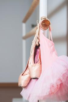 子バレエドレスとバレエバレを保持しているバレエシューズ。ダンスのコンセプト。