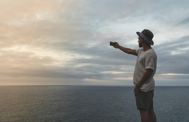 Человек фотографируя к океану на заходе солнца.
