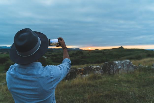 Человек фотографируя на заходе солнца в горе.