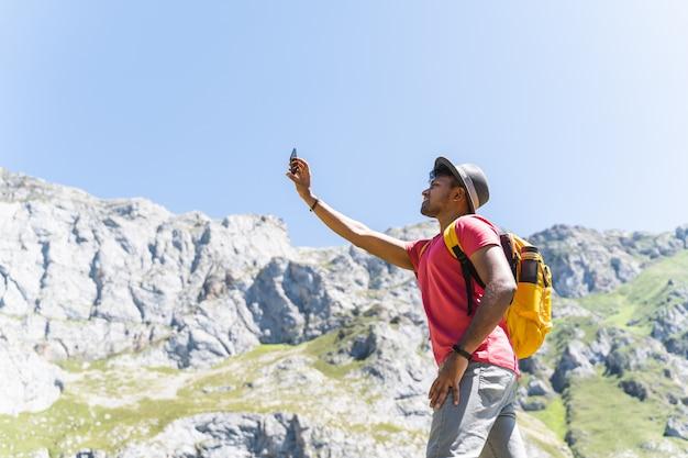ハイキングと写真を撮る山に黄色のバックパックを運ぶインド人。