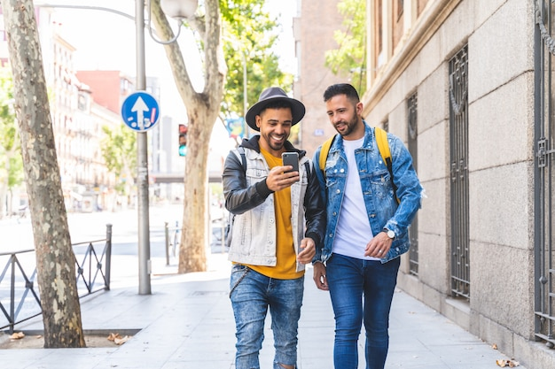 Два друга мужского пола, идущие вместе на улице, используя сотовый телефон.