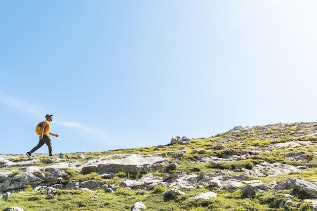 バックパックを身に着けている山でのハイキングラテンアメリカ人。