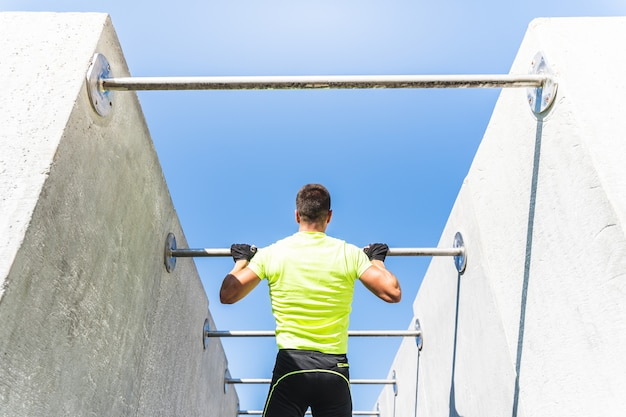 屋外プルアップバーで体操を行う若い男。