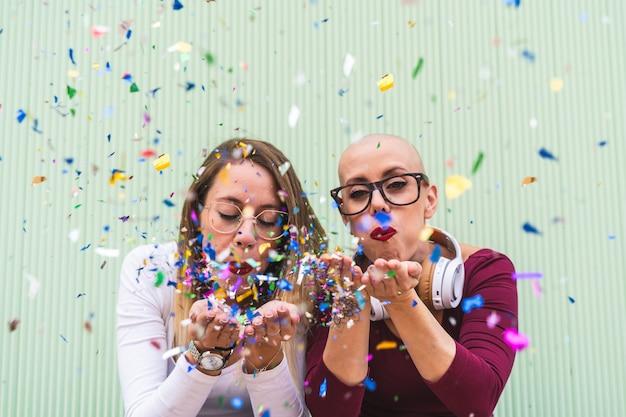 Две подруги, дует конфетти на открытом воздухе.