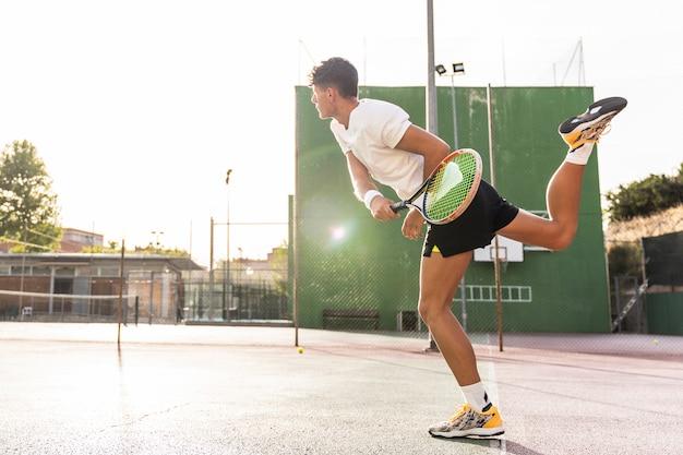 Молодой человек, играя в теннис на открытом воздухе.