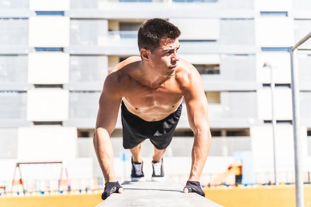 若い男が屋外でトレーニングします。