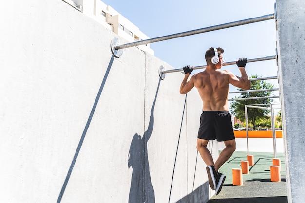 屋外のプルアップバーでトレーニング体操を行う若い男。