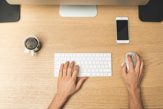 自宅のコンピューターで作業する人間の手の天頂ビュー。
