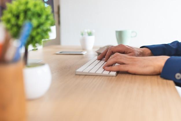 自宅のコンピューターで作業する人間の手のクローズアップ。