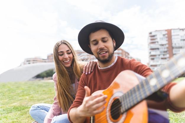 屋外でギターを弾く友人のグループ