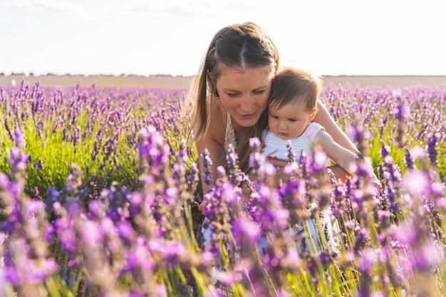 Мать и ребенок с удовольствием в поле цветов.
