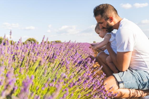 Испанский отец с дочерью, с удовольствием в поле цветов.