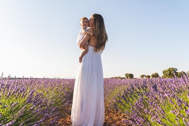 Мать и дочь с удовольствием в поле цветов на открытом воздухе.