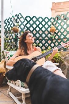 Красивая женщина играет на гитаре на открытом воздухе