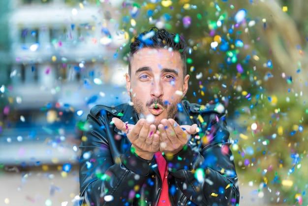 Красивый мужчина дует конфетти на открытом воздухе.
