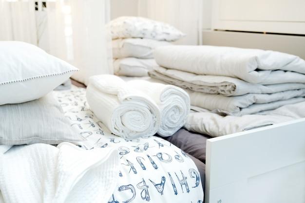 ホテルのベッドリネンとタオル。モダンなインテリアの寝室のベッドの上の清潔なタオル。