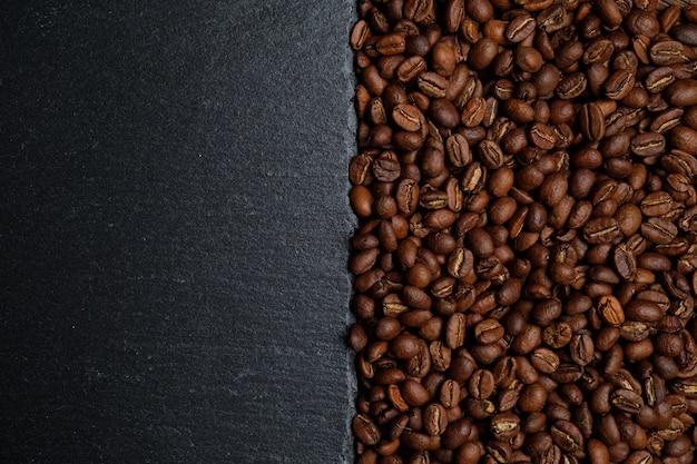 コーヒー豆とコピースペースのスレートからの背景。上面図。