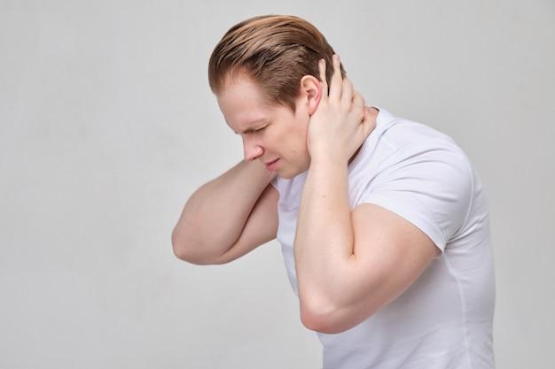 白いシャツを着た男が首をマッサージします。頸椎の骨軟骨症による痛み。