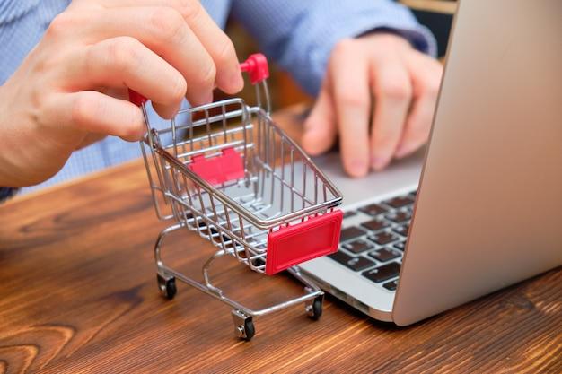 男はラップトップでシャツに座って、トロリーを保持しています。インターネットでの卸売購入の概念。