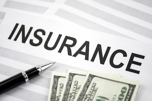 印刷単語保険と紙の上のドルで横になっているペン
