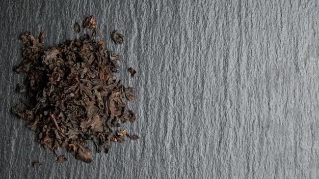 Куча разбросанного черного чая на фоне каменной плиты