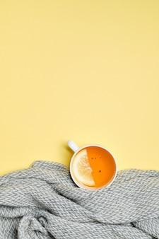 レモン、黄色の表面にグレーのスカーフのスライスと紅茶のカップ
