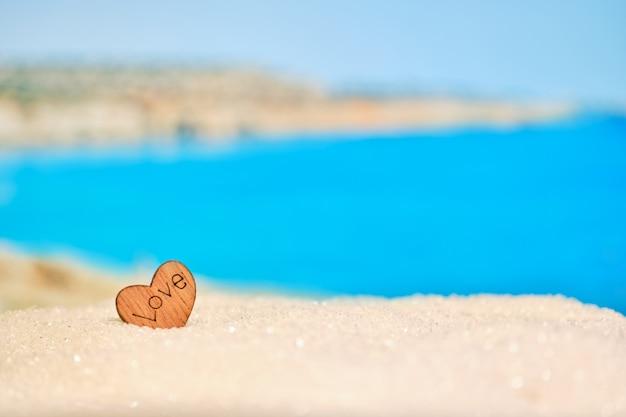 Красивый размытый вид на пляж с деревянным сердцем в песке. концепция любимого места для путешествий.