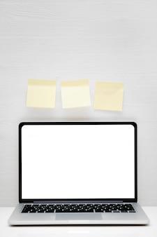 黄色のステッカーと白い木製の背景にコピースペースのための場所のノート。垂直。