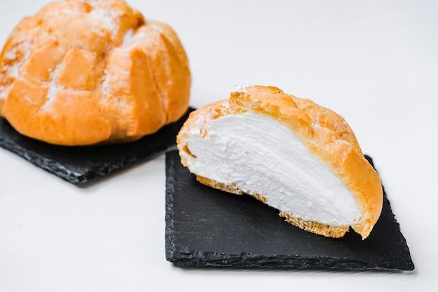 シェール皿と木製の背景にクリームでカットの甘いパン。