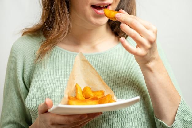 Девушка держит тарелку и ест деревенский картофель в бумаге.