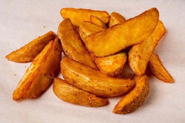 Деревенский жареный картофель на фоне бумаги.