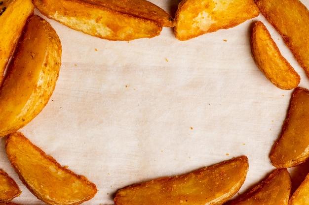 Деревенский жареный картофель на фоне бумаги в виде рамы. вид сверху.